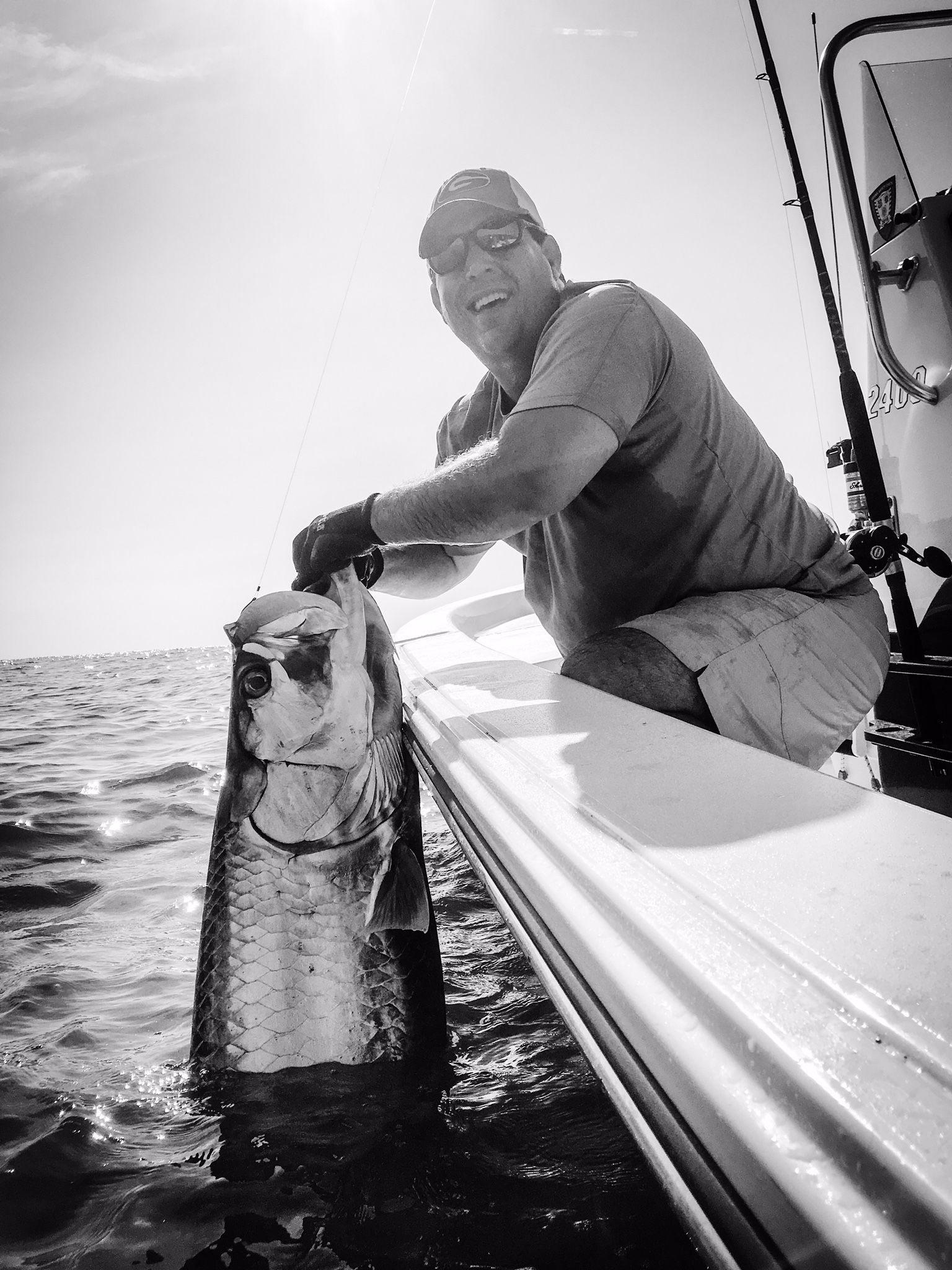 Fisherman with large Tarpon caught off side of boat