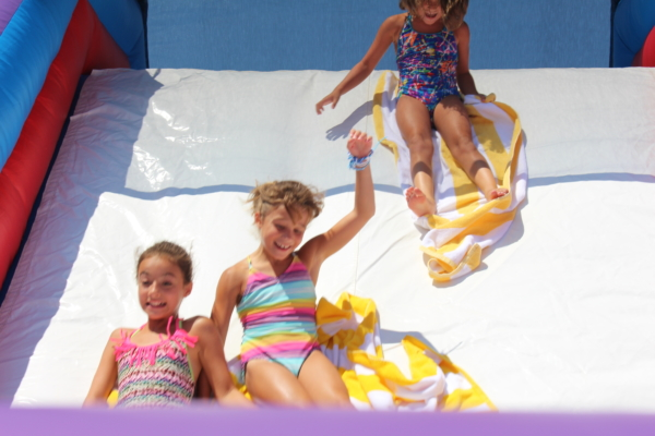 Children sliding on towels down slide